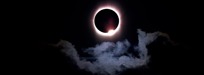 The sun in total solar eclipse with cloud in foreground