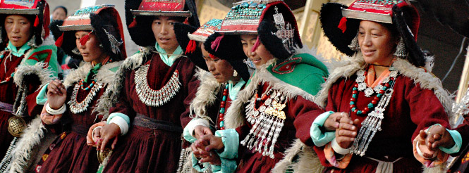 Six Ladakhi women with turquoise headresses and silver necklaces