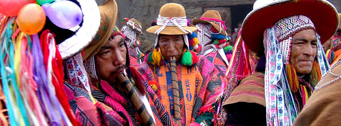 Three Andean flute players in traditional dress at a festival