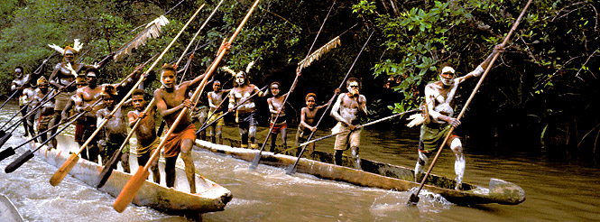papua new guinea villagers paddling dugout canoes